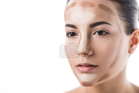 beautiful girl with foundation cream on face looking away isolated on white