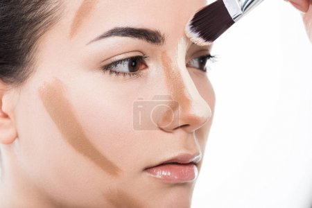 cropped image of visagiste doing makeup for girl isolated on white