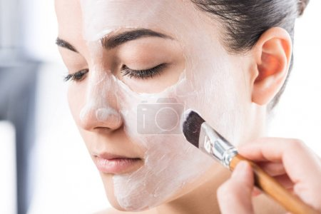 cropped image of beautician applying cream on girl face isolated on white