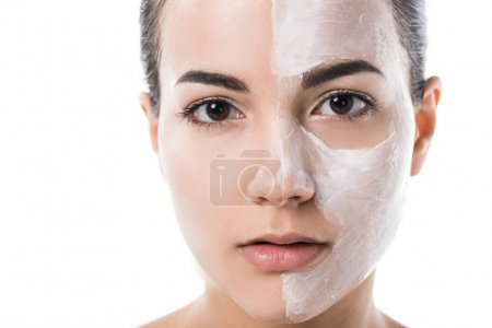 beautiful girl with cream on half of face looking at camera isolated on white