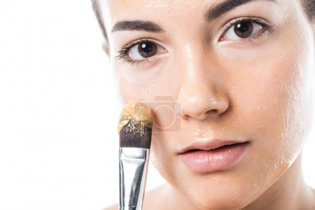 beautiful girl applying honey mask on face with brush isolated on white