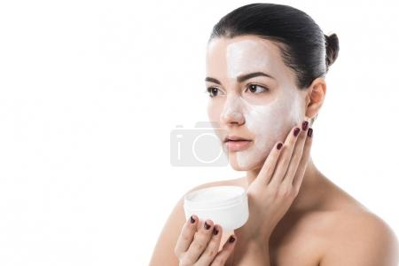 beautiful girl applying cream on face isolated on white