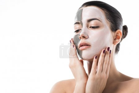 beautiful girl with different cosmetic facial masks touching face isolated on white