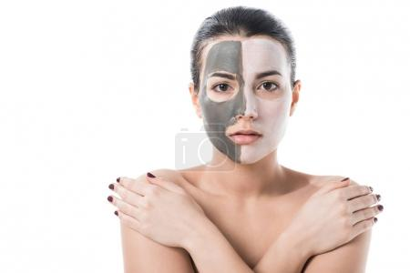 beautiful girl with different cosmetic facial masks looking at camera isolated on white