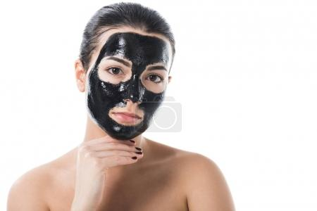 attractive girl in cosmetic black clay facial mask looking at camera isolated on white