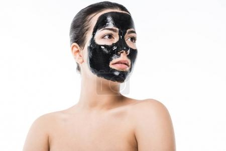 beautiful girl in cosmetic black clay facial mask looking away isolated on white