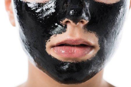 Photo pour Image recadrée de jeune fille avec masque facial de cosmétique noir isolé sur blanc - image libre de droit