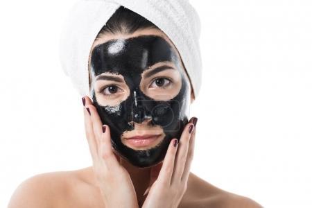 Photo pour Belle fille en masque facial argile noire cosmétique, regardant la caméra isolé sur blanc - image libre de droit