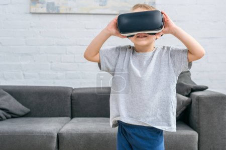 Little boy using virtual reality headset in front of sofa