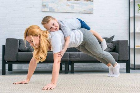 Photo pour Mère, faisant la planche avec petit fils sur le dos - image libre de droit