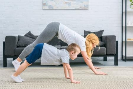 Side view of mother and son in adho mukha svanasana position on yoga mats