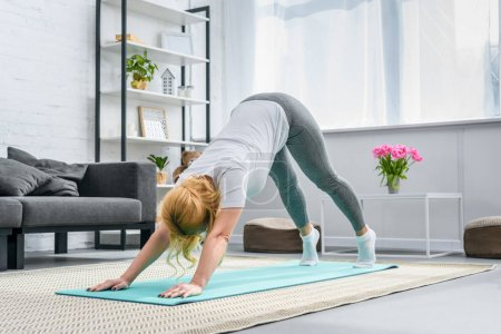 Woman in downward facing dog position on yoga mat