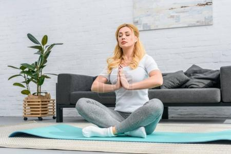 Young woman practicing in lotus position on yoga mat
