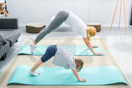 Mother and little boy practicing downward facing dog position on yoga mats
