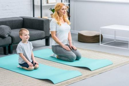 Smiling boy and mother resting on yoga mats