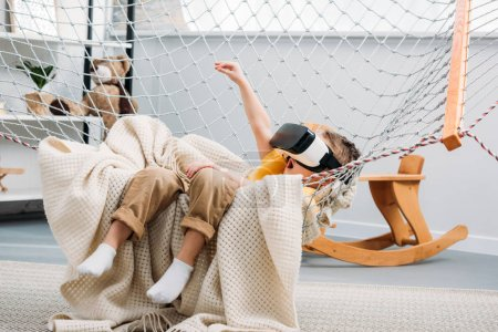 Child in boy hammock using virtual reality headset