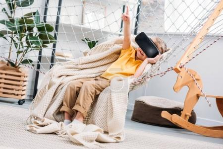 Little boy in rope hammock using virtual reality headset