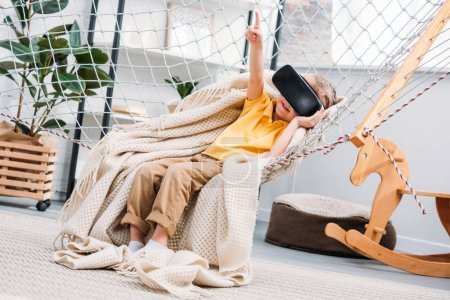 Little boy in rope hammock using virtual reality headset