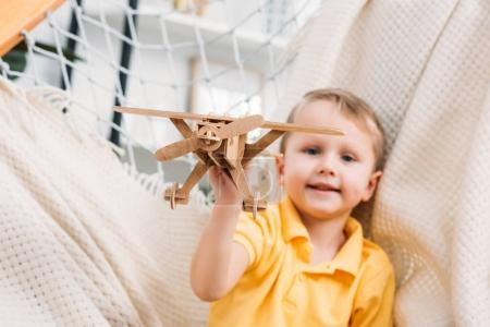 Little boy playing with wooden airplane toy