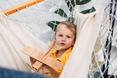 Photo for Little boy playing with wooden airplane toy in hammock - Royalty Free Image