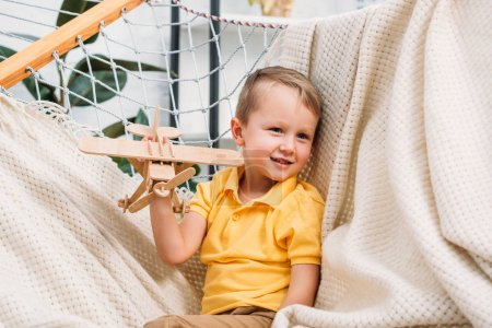 Photo for Smiling boy playing with wooden airplane toy in hammock - Royalty Free Image