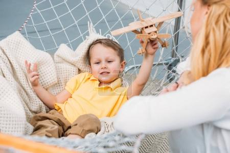Cropped image of woman and little boy playing with wooden airplane toy in hammock
