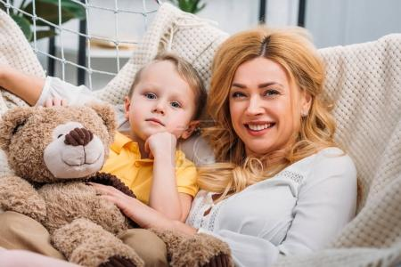 Photo for Happy mother and little son laying in hammock with teddy bear - Royalty Free Image