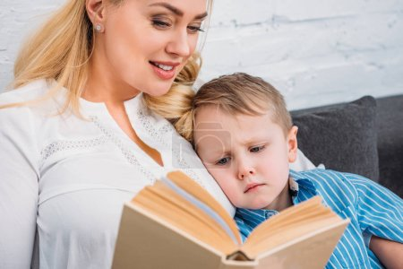 Mother reading book to upset little son