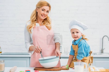 Photo for Little boy and mother cooking together in kitchen - Royalty Free Image