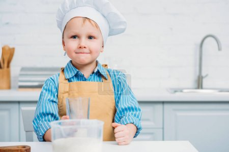 Boy in cooking hat and apron holding glass in kitchen