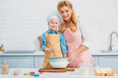 Smiling mother and son in kitchen cooking together