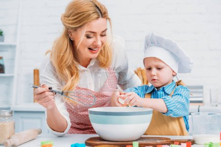 Photo for Smiling mother with hand beater and little boy pouring egg into bowl - Royalty Free Image