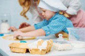 Eggs, milk and butter with mother and son rolling dough behind