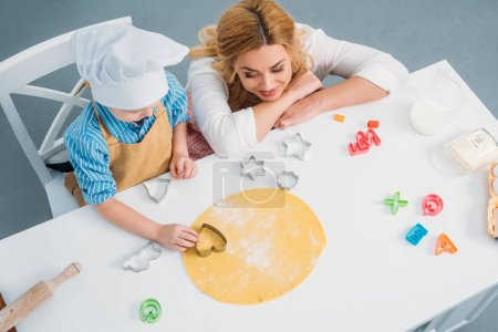 High angle view of mother and son using cooking mold on dough