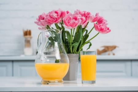Front view of orange juice and vase with pink tulips on table in modern kitchen