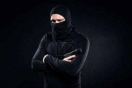 Thief in black balaclava holding gun in folded arms on black
