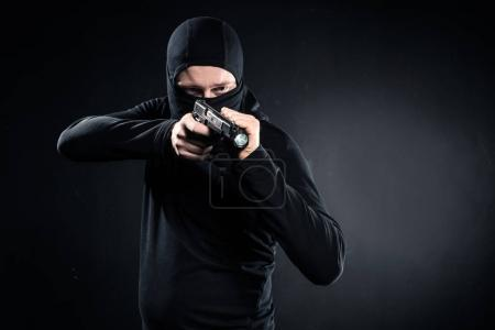Robber in balaclava aiming with gun on black