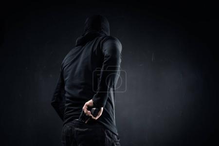 Photo pour Un voleur caché derrière son dos - image libre de droit