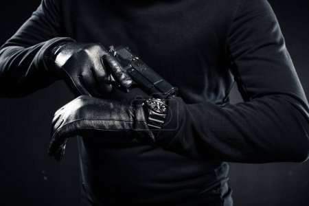Man in gloves with gun checking his watch