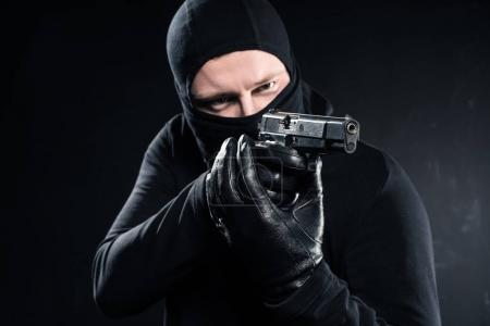 Male robber in balaclava aiming with gun on black