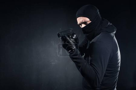 Male criminal in balaclava and gloves aiming with gun on black