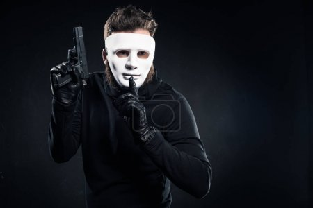 Thief in mask holding gun and showing silence gesture