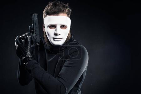 Criminal in white mask and black clothes holding gun