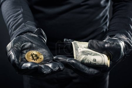 Close-up view of dollars and bitcoin in hands of thief