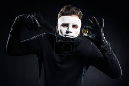 Man in white mask holding gun and golden bitcoin