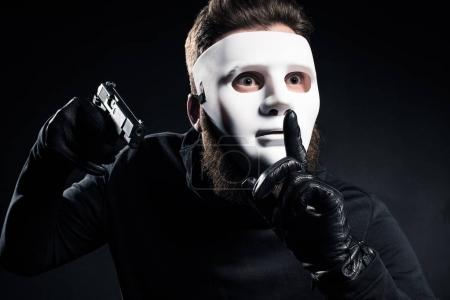 Robber in mask holding gun and showing silence gesture