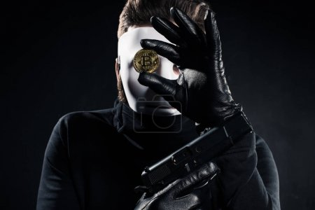 Thief in white mask holding gun and golden bitcoin