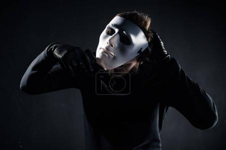 Male criminal taking white mask off his face