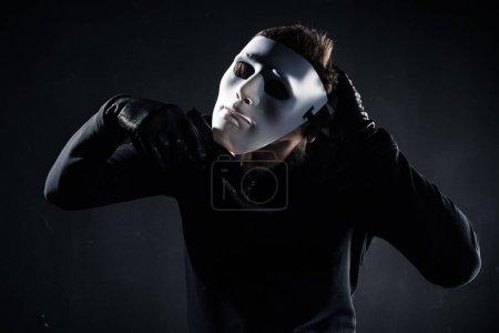 Photo pour Criminel mâle prenant un masque blanc sur son visage - image libre de droit