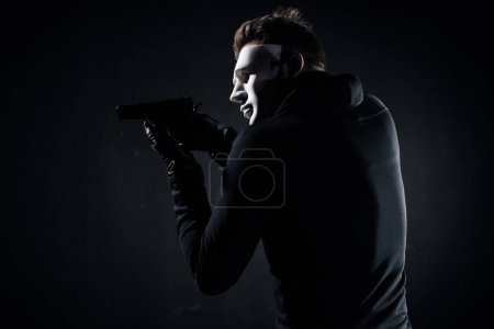 Robber in mask and gloves aiming with gun on black